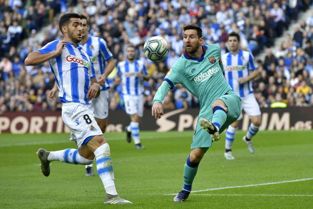 Barcelona's Lionel Messi kicks the ball in front of Real Sociedad's Mikel Merino, right, during the Spanish La Liga soccer match between Real Sociedad and Barcelona, at Anoeta stadium, in San Sebastian, Spain, Saturday, Dec. 14, 2019. (AP Photo/Alvaro Barrientos)