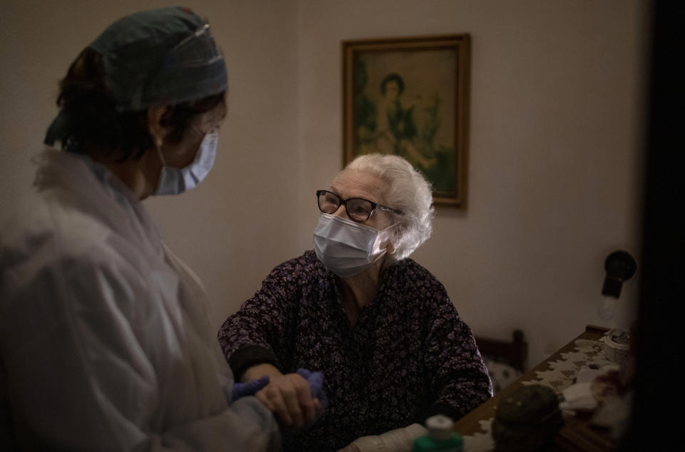 Pepita Jove Puiggros, 92, holds the hand of home care nurse Laura Valdes during a visit in Barcelona, Spain, April 2, 2020. Puiggros lives alone and receives food deliveries from a social service agency three days a week, but the deliveries have become more unpredictable amid the coronavirus pandemic. (AP Photo/Emilio Morenatti)