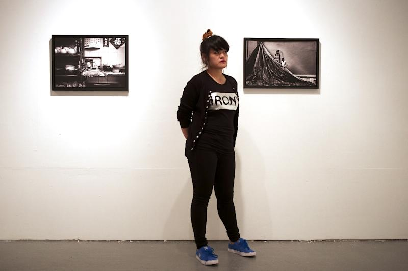 Filipino photographer Xyza Cruz Bacani poses with her work in Macau on March 21, 2015 (AFP Photo/Aaron Tam)
