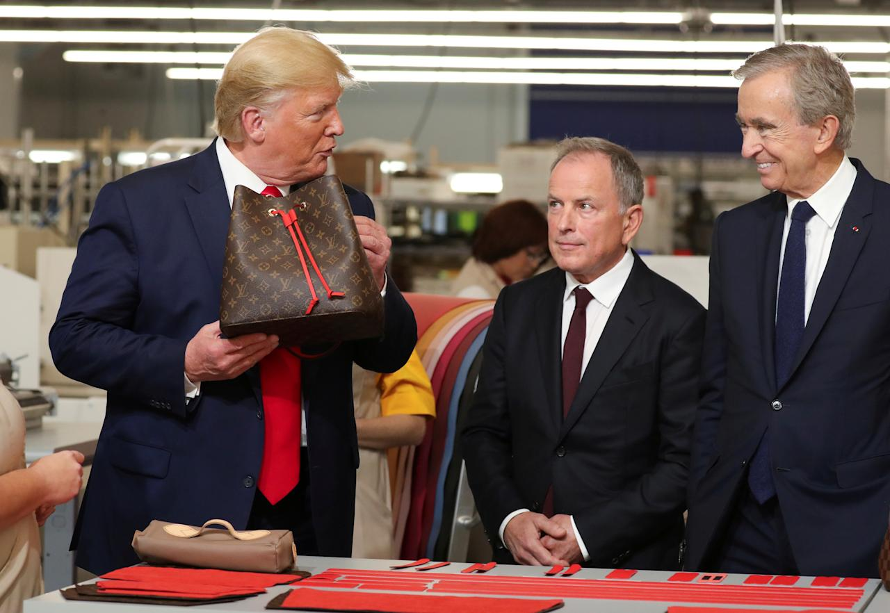 U.S. President Donald Trump holds a purse as Louis Vuitton's CEO Michael Burke and Chairman and CEO of Luxury goods group LVMH Bernard Arnault look on during a visit to the Louis Vuitton Rochambeau Ranch leather workshop in Keene, Texas, U.S. October 17, 2019. REUTERS/Jonathan Ernst     TPX IMAGES OF THE DAY