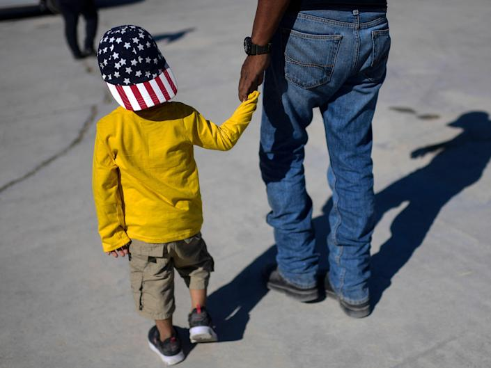 Haitian migrant holding hand of child wearing an American flag, stars-and-stripes, hat.