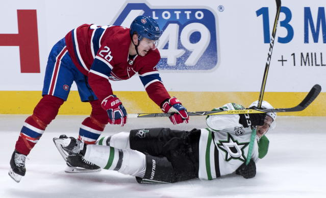 Montreal Canadiens defenseman Mike Reilly (28) sends Dallas Stars centre Tyler Pitlick (18) to the ice during the second period of an NHL hockey game in Montreal on Tuesday, March 13, 2018. (Paul Chiasson/The Canadian Press via AP)
