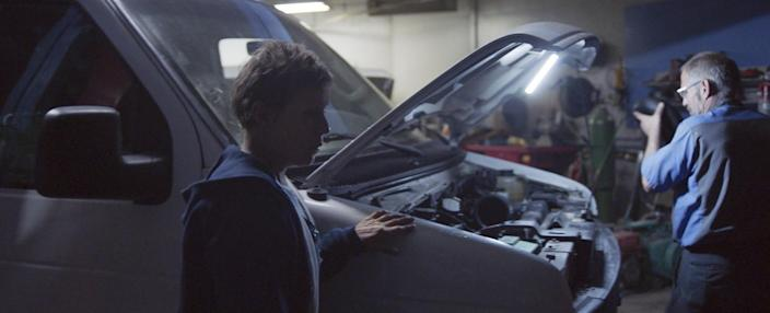 A film still shows actress Frances McDormand with her hand on a van, its hood up as a mechanic works.