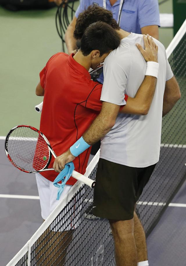 Serbia's Novak Djokovic, left, and Juan Martin del Potro of Argentina embrace each other after their singles final match of the Shanghai Masters tennis tournament at Qizhong Forest Sports City Tennis Center, in Shanghai, China, Sunday, Oct. 13, 2013. Djokovic won 6-1, 3-6, 7-6 (3). (AP Photo/Eugene Hoshiko)