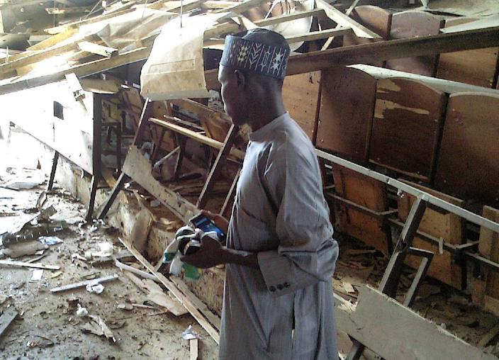 A student looks over at the damage to a lecture hall at the Federal College of Education in the northern Nigerian city of Kano, on September 17, 2014 (AFP Photo/Aminu Abubakar)