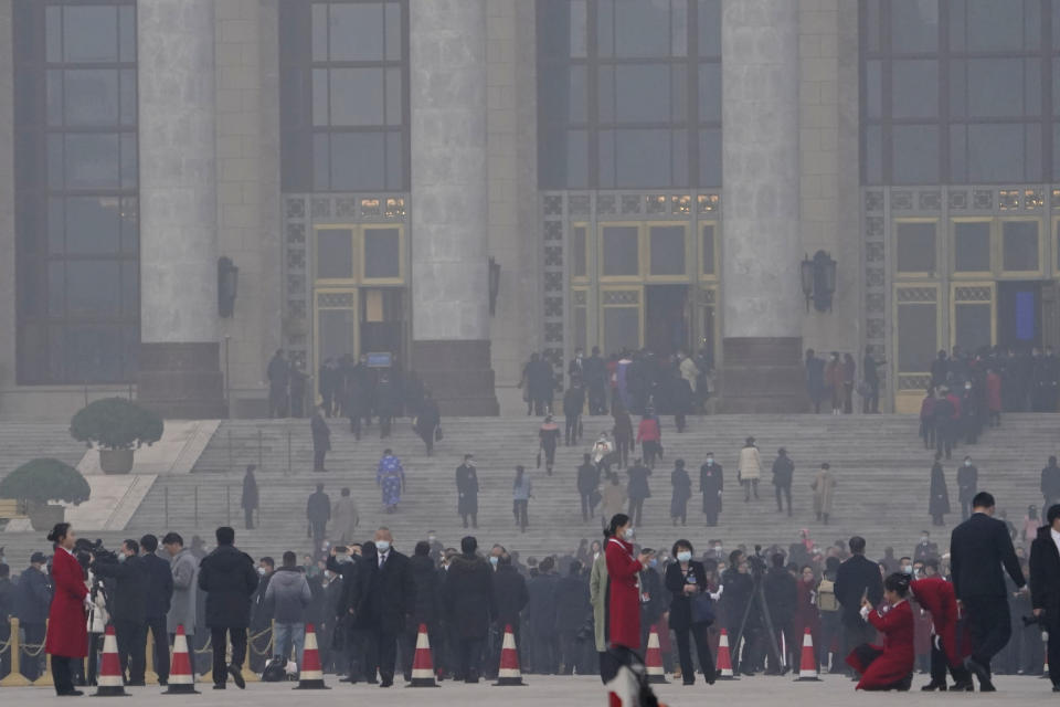 """Delegates arrive at the Great Hall of the People for the opening session of the annual National People's Congress held in Beijing on Friday, March 5, 2021. The ruling Communist Party is aiming for economic growth """"over 6%"""" as it rebounds from the coronavirus pandemic, Premier Li Keqiang said in a speech at China's ceremonial legislature Friday. (AP Photo/Ng Han Guan)"""