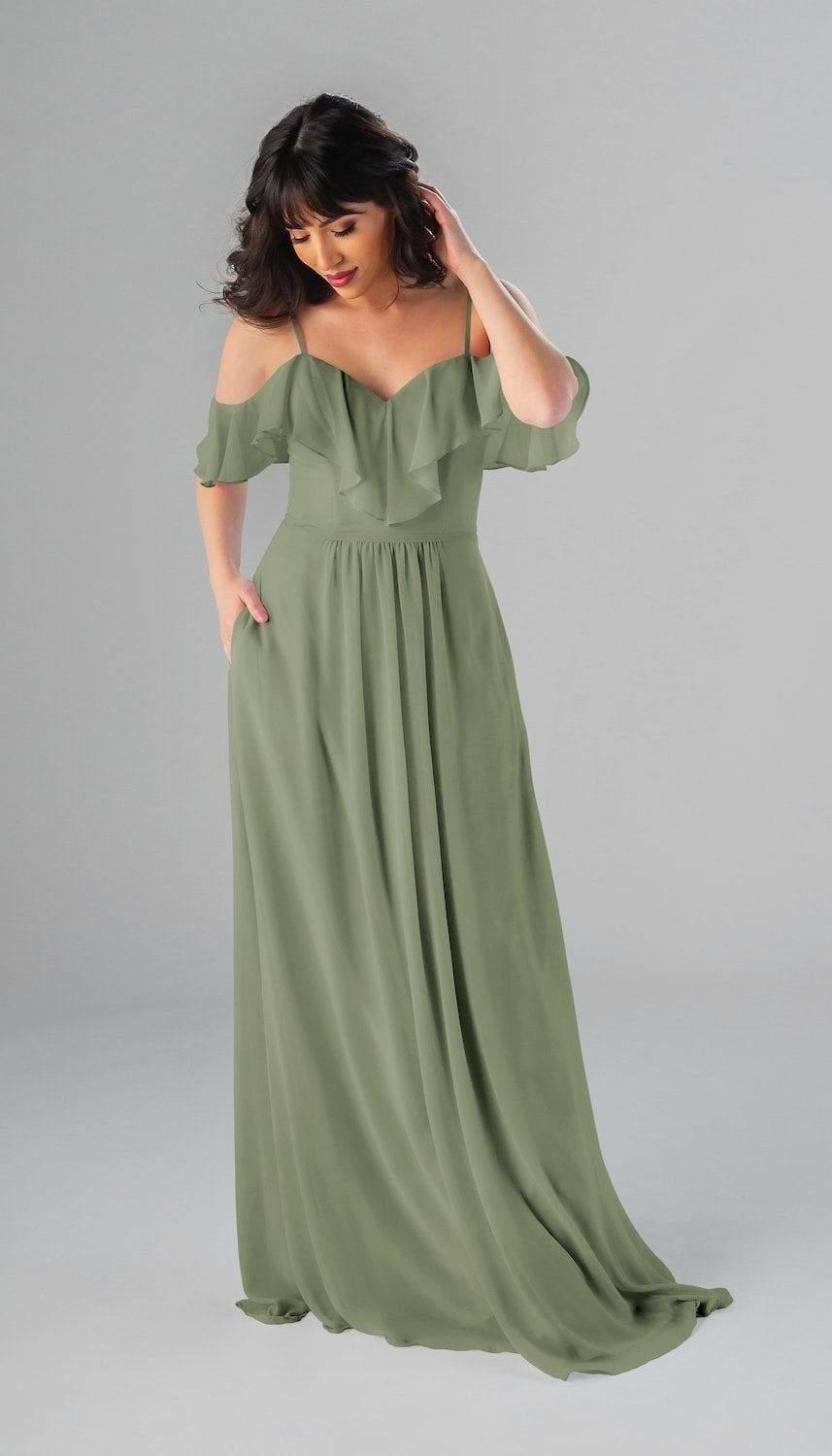 brunette model looking down posing in green bridesmaids dress with ruffles