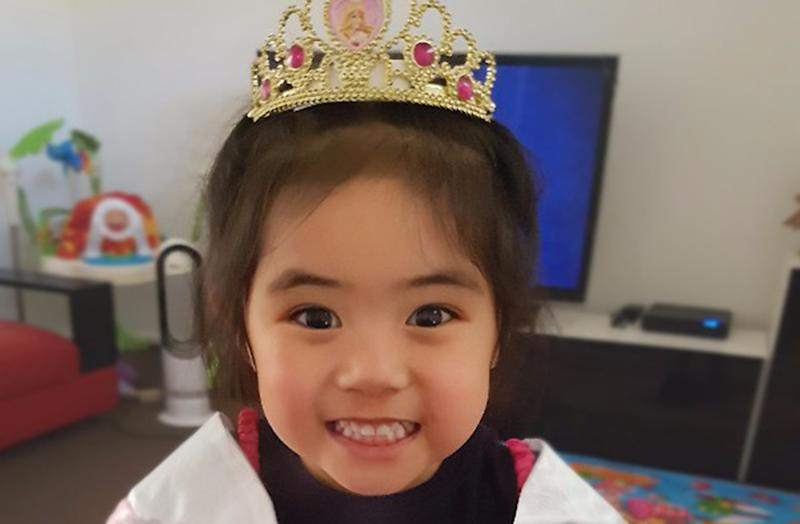 Three-year-old Caitlin Cruz pictured smiling and wearing princess crown.