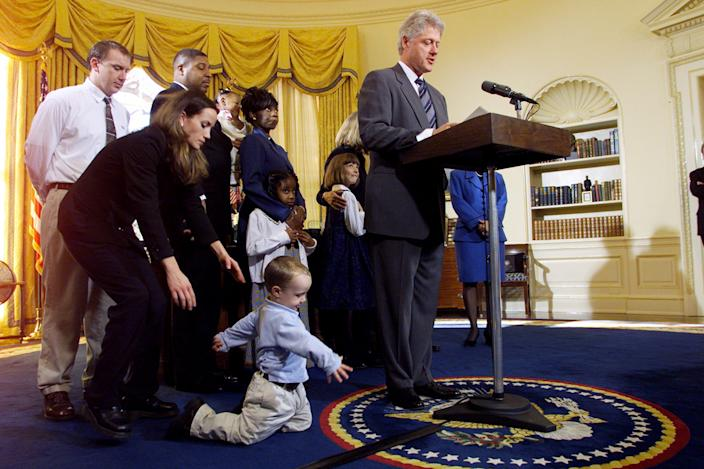 UNITED STATES - NOVEMBER 30:  Katie Banks reaches for her son, Collin, who's not paying much attention to President Bill Clinton in the Oval Office. Collin's father, Eric (left), and members of other families look on as Clinton announces an order allowing states to develop paid-leave programs for parents who have newborns or recently adopted children.  (Photo by Harry Hamburg/NY Daily News Archive via Getty Images)