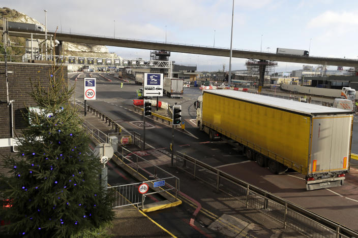 A truck passes a Christmas tree as it enters The Port of Dover in Kent, England, Friday, Dec. 25, 2020. Thousands wait to resume their journey across The Channel after the borders with France reopened. Trucks inched slowly past checkpoints in Dover and headed across the Channel to Calais on Thursday after France partially reopened its borders following a scare over a rapidly spreading new virus variant. (AP Photo/Kirsty Wigglesworth)