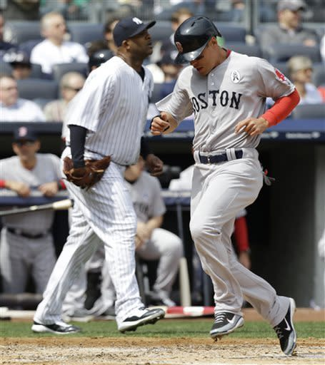 Boston Red Sox runner Jacoby Ellsbury, right, scores in front of New York Yankees starting pitcher CC Sabathia, left, on Dustin Pedroia's second-innning, RBI single in an Opening Day baseball game at Yankee Stadium in New York, Monday, April 1, 2013. (AP Photo/Kathy Willens)