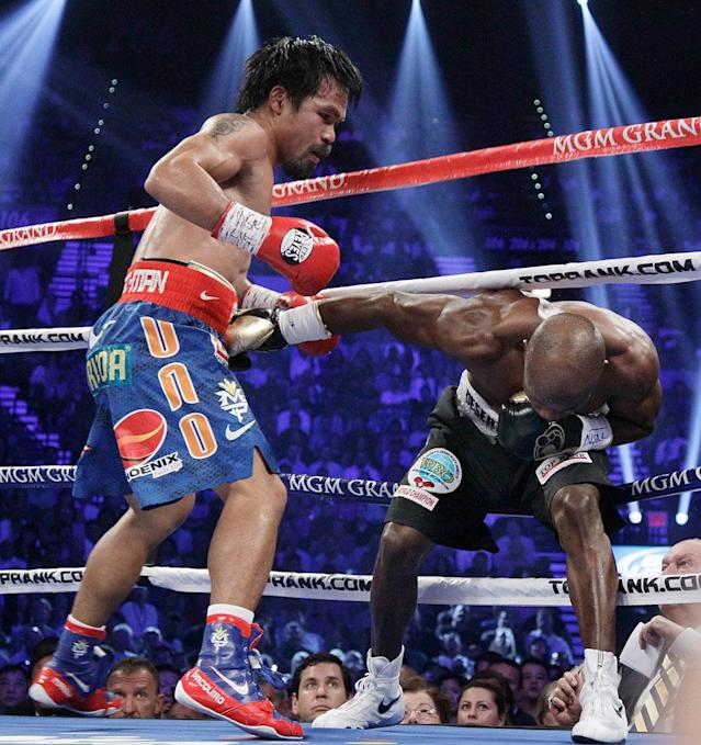 Manny Pacquiao, left, from the Philippines, drives Timothy Bradley, from Palm Springs, Calif., into the ropes in the third round of their WBO welterweight title fight Saturday, June 9, 2012, in Las Vegas.