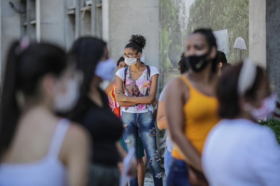 RIO DE JANEIRO, BRAZIL - JANUARY 17:  Students wearing protective masks wait in line at the Rio de Janeiro State University (UERJ) for the National High School Exam (ENEM) on January 17, 2021 in Rio de Janeiro, Brazil. Despite 15 Brazilian states showing an increase in the number of deaths from Coronavirus (Covid-19), the government maintained the exam and 5.7 million candidates are confirmed.  (Photo by Andre Coelho/Getty Images)