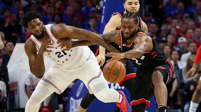 Toronto Raptors' Kawhi Leonard, right, reaches for the ball as he holds off Philadelphia 76ers' Joel Embiid. (AP Photo/Chris Szagola)