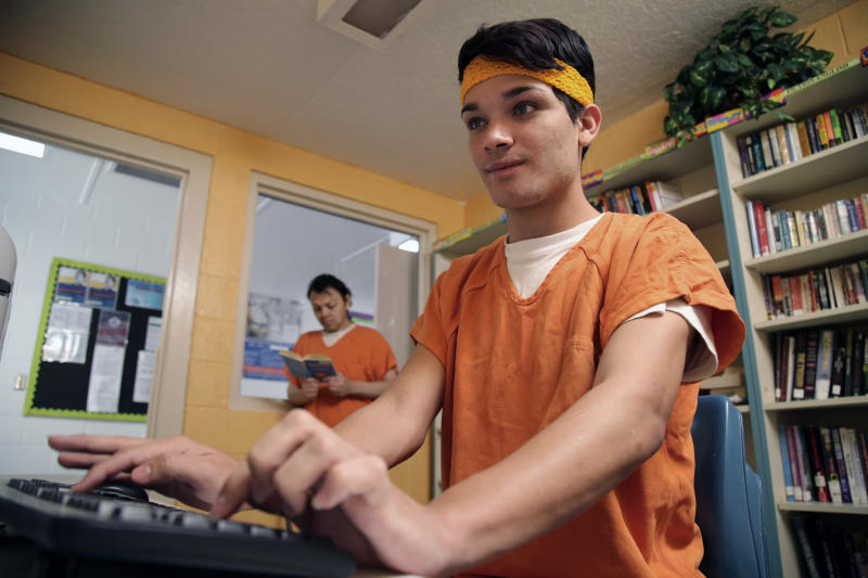 This June 6, 2019 image provided by U.S. Immigration and Customs Enforcement shows immigration detainees using the law library at a dedicated unit for transgender migrants in the Cibola County Correctional Center in Milan, N.M. (Ron Rogers/U.S. Immigration and Customs Enforcement via AP)