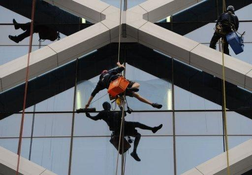 Workers clean windows on a Sydney high rise building on July 12, 2012. Australia's unemployment rate rose to 5.2 percent in June, with the economy shedding 27,000 jobs as global uncertainty and the strong Australian dollar weighed on employers