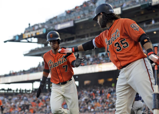 San Francisco Giants' Gorkys Hernandez (7) is high-fived by teammate Brandon Crawford (35) after scoring on a wild pitch during the first inning of a baseball game against the San Diego Padres, Friday, June 22, 2018, in San Francisco. (AP Photo/Marcio Jose Sanchez)