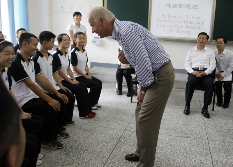 FILE - In this Aug. 21, 2011, file photo. U.S. Vice President Joe Biden, center, talks to students as Chinese Vice President Xi Jinping, second from right, watches during their visit to the Qingchengshan High School in Dujiangyan in southwestern China's Sichuan province, Sunday, Aug. 21, 2011. It's up to Biden to show the U.S. effort to realign its gaze to the East hasn't fizzled out. When he arrives Dec. 2, 2013, in Tokyo on a weeklong trip to Asia, he'll step into a region that's carefully watching to see how committed he and President Barack Obama are to increasing America's influence in Asia, as a hedge against China and its increasing assertiveness. Huddling with foreign leaders in Japan, China and South Korea, Biden will seek to show that despite focusing intensely on Mideast flare-ups and a host of domestic distractions, the U.S. still intends to be a Pacific power. (AP Photo/Ng Han Guan, Pool)