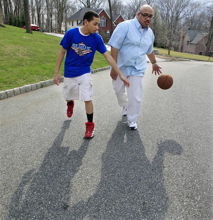 "In this Friday, March 23, 2012 photo, Bill Stephney and son Trevor, 13, play with a basketball near their home in Randolph Township, N.J. Stephney, a media executive who lives in a New Jersey suburb that is mostly white and Asian, has two sons, ages 18 and 13. The killing of Trayvon Martin was an opportunity for him to repeat a longtime lesson: black men can get singled out, ""so please conduct yourself accordingly."" (AP Photo/Mel Evans)"