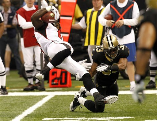 Atlanta Falcons wide receiver Julio Jones (11) is tripped up by New Orleans Saints cornerback Jabari Greer (33) on a pass play in the first quarter of an NFL football game in New Orleans, Monday, Dec. 26, 2011. (AP Photo/Gerald Herbert)