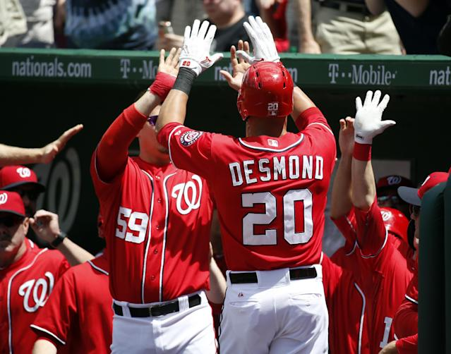 Washington Nationals' Ian Desmond (20) celebrates his solo home run with his teammates during the second inning of a baseball game against the New York Mets at Nationals Park Sunday, May 18, 2014, in Washington. (AP Photo/Alex Brandon)