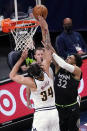 Denver Nuggets' JaVale McGee (34) breaks up a layup attempt by Minnesota Timberwolves' Karl-Anthony Towns (32) during the first half of an NBA basketball game Thursday, May 13, 2021, in Minneapolis. (AP Photo/Jim Mone)