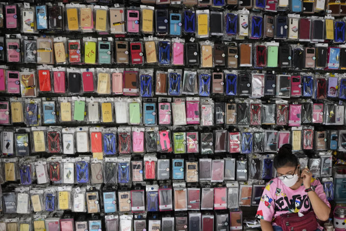 A mobile phone case vendor wearing a protective mask to help curb the spread of the coronavirus waits for customers in Bangkok, Thailand, Tuesday, Sept. 14, 2021. (AP Photo/Sakchai Lalit)