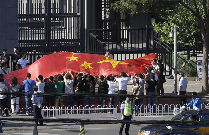 Chinese protesters hold up a giant Chinese national flag and chant slogans outside the Japanese embassy in Beijing, China, Wednesday, Sept. 12, 2012. A territorial flare-up between China and Japan intensified as two Beijing-sent patrol ships arrived near disputed East China Sea islands in a show of anger over Tokyo's purchase of the largely barren outcroppings from their private owners. (AP Photo/Ng Han Guan)