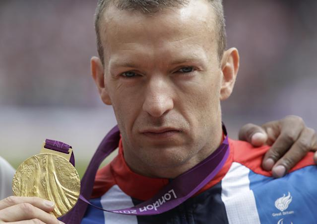 Britain's Richard Whitehead poses for the photographers with his gold medal after winning the gold medal at men's 200m T42 final race at the 2012 Paralympics in London, Saturday, Sept. 1, 2012. (AP Photo/Lefteris Pitarakis)