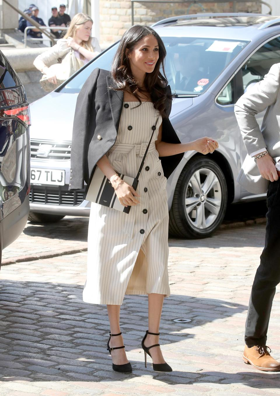 <p>For her first major royal engagement, the Duchess of Sussex broke protocol in a striped dress by Altuzarra with a Camilla and Marc blazer draped across her shoulders blogger-style. <em>[Photo: Getty]</em> </p>