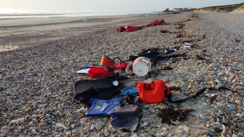 Life jackets, a petrol tank, a foot inflator, migrants' belongings and a damaged dinghy are seen on the beach in Wimereux