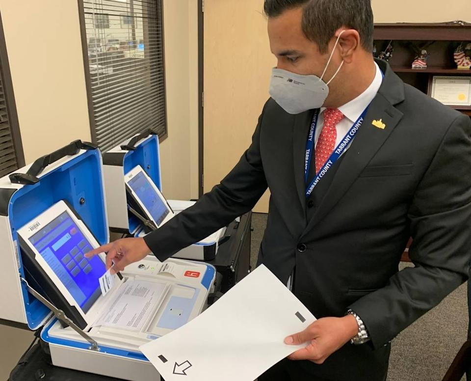 Heider Garcia, Tarrant County election administrator, demonstrates how to use a voting machine.