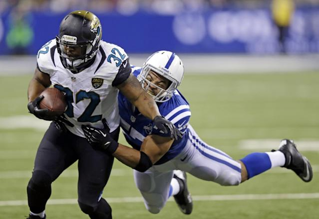 Jacksonville Jaguars' Maurice Jones-Drew (32) is tackled by Indianapolis Colts' Josh McNary (57) during the second half of an NFL football game on Sunday, Dec. 29, 2013, in Indianapolis. (AP Photo/Michael Conroy)