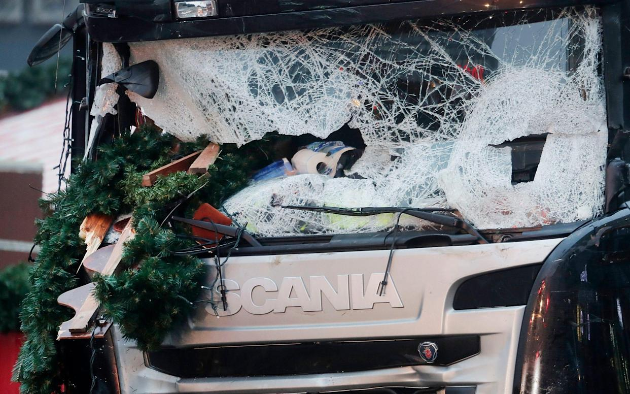 Debris is seen wedged in the smashed windscreen of a lorry, which was driven into a Christmas market in Berlin in 2016 - AP