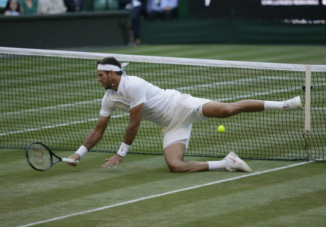 Juan Martin Del Potro of Argentina falls on the court during the men's quarterfinal match against Rafael Nadal of Spain at the Wimbledon Tennis Championships in London, Wednesday July 11, 2018. (AP Photo/Tim Ireland)