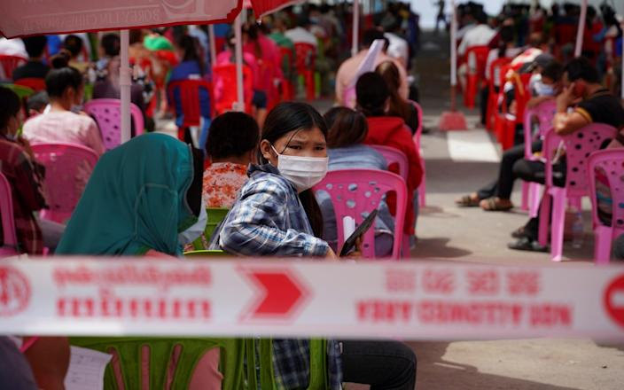People wait to get tested inside a red zone in Phnom Penh - Reuters