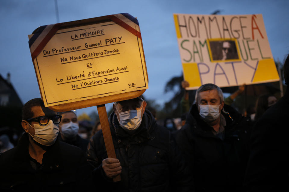 People attend a memorial march in homage to the history teacher who was beheaded last week, Tuesday, Oct.20, 2020 in Conflans-Sainte-Honorine, northwest of Paris. Samuel Paty was beheaded on Friday by an 18-year-old Moscow-born Chechen refugee, who was later shot dead by police. Police officials said Paty had discussed caricatures of Islam's Prophet Muhammad with his class, leading to threats. Placard at left reads: Teacher Samuel Paty's memory will not disappear, neither will freedom of speech. (AP Photo/Lewis Joly)