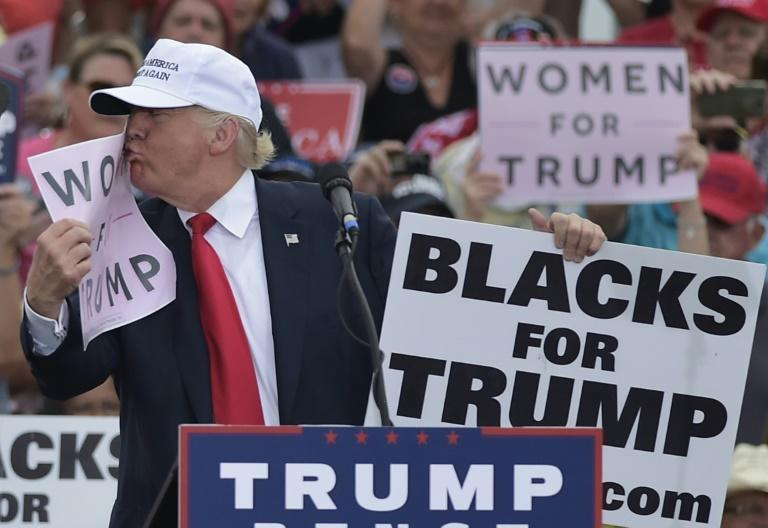 "File photo shows then Republican presidential nominee Donald Trump kissing a ""Women for Trump"" placard during a rally in Florida"