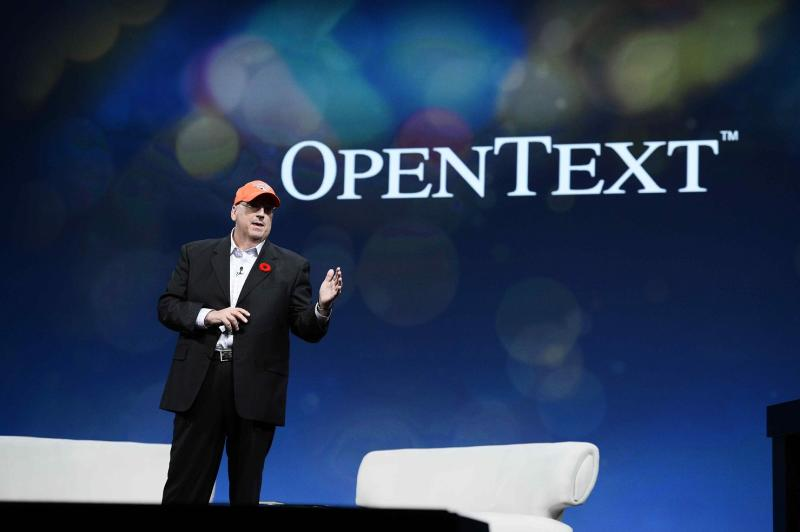 Person wearing hat on a stage with OpenText logo behind him.
