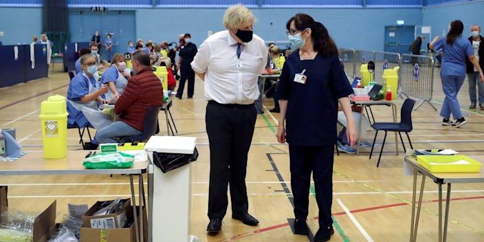 Britain's Prime Minister Boris Johnson speaks with health worker Wendy Warren during his visit at a coronavirus disease (COVID-19) vaccination centre at Cwmbran Stadium in Cwmbran, South Wales, Britain February 17, 2021. Geoff Caddick/Pool via REUTERS