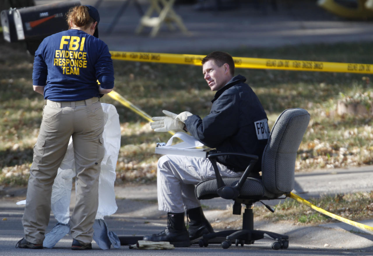 FBI investigators don clean overalls while searching the home of missing baby Lisa Irwin in Kansas City, Mo., Wednesday, Oct. 19, 2011. (AP Photo/Orlin Wagner)