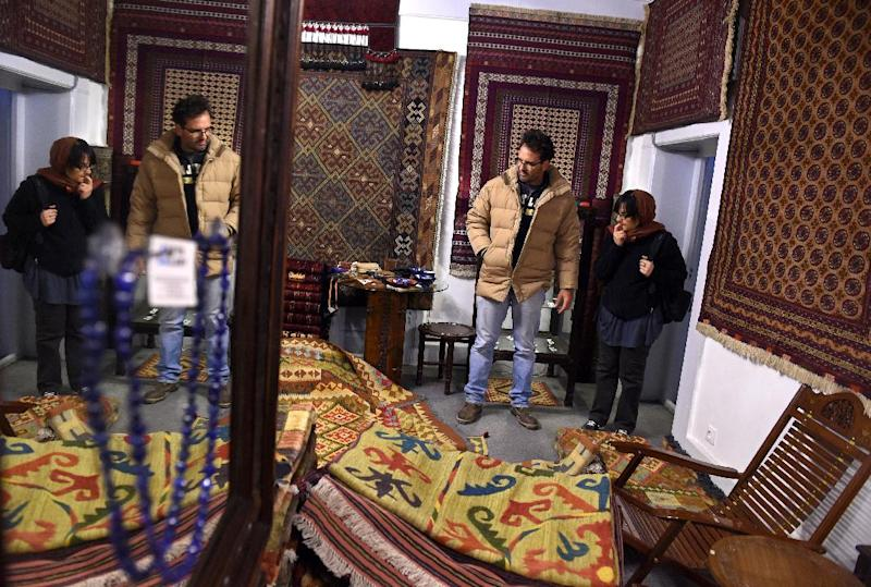 Foreign visitors look at handmade carpets at a shop in The Gangina Centre, at Shahr-e-Naw in Kabul, on December 2, 2014 (AFP Photo/Wakil Kohsar)