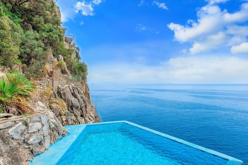 """<p>This sprawling villa in the heart of the Amalfi Coast is a real Italian gem. Built using natural stone, it has five good-sized <a href=""""https://www.housebeautiful.com/uk/decorate/bedroom/a37178362/redesign-bedroom-moodboard/"""" rel=""""nofollow noopener"""" target=""""_blank"""" data-ylk=""""slk:bedrooms"""" class=""""link rapid-noclick-resp"""">bedrooms</a>, a swimming pool, its own private beach, and a lift which makes journeying from top to bottom a real breeze. </p><p>This property is currently on the market for €6.5 million with Italy Sotheby's International Realty via <a href=""""https://www.rightmove.co.uk/properties/77331254#/"""" rel=""""nofollow noopener"""" target=""""_blank"""" data-ylk=""""slk:Rightmove"""" class=""""link rapid-noclick-resp"""">Rightmove</a>. </p>"""
