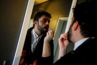 Cayan Hakiki applies make-up in front of a mirror at their home in Ankara
