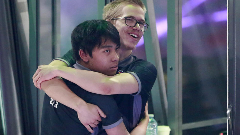 Anathan Pham (L) and Topias Taavitsainen of OG hug after their 3-2 win over PSG.LGD in their grand final Dota 2 match. (Photo by Jeff Vinnick/Getty Images)