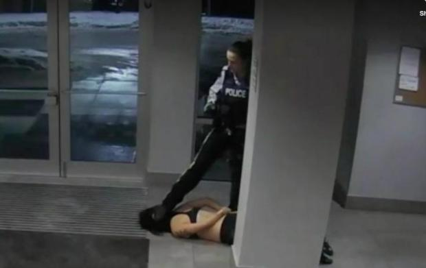 Still from a surveillance video shows Const. Lacy Browning stepping on student Mona Wang's head after a wellness check by the RCMP  Jan. 20. (Submitted by Bridge Law Corporation - image credit)