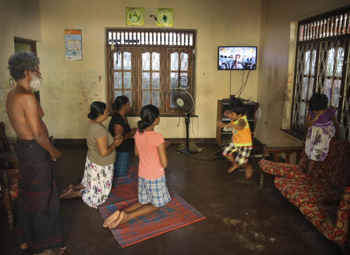 A Sri Lankan Christian catholic family prays as children play inside their home watching live transmission of Sri Lankan Archbishop Cardinal Malcolm Ranjith, in Negombo, Sri Lanka, Sunday, April 28, 2019. Sri Lanka's Catholics celebrated Sunday Mass in their homes by a televised broadcast as churches across the island nation shut over fears of militant attacks, a week after the Islamic State-claimed Easter suicide bombings killed over 250 people. (AP Photo/Manish Swarup)