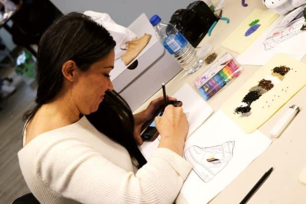 A workshop participant works on their sneaker design.
