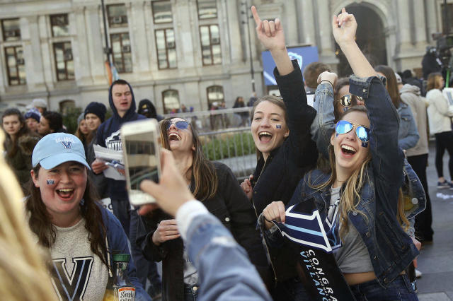 Fans cheer as they take a picture at Dilworth Plaza before Villanova's NCAA men's basketball tournament victory parade, Thursday, April 5, 2018, in Philadelphia. (Tim Tai/The Philadelphia Inquirer via AP)