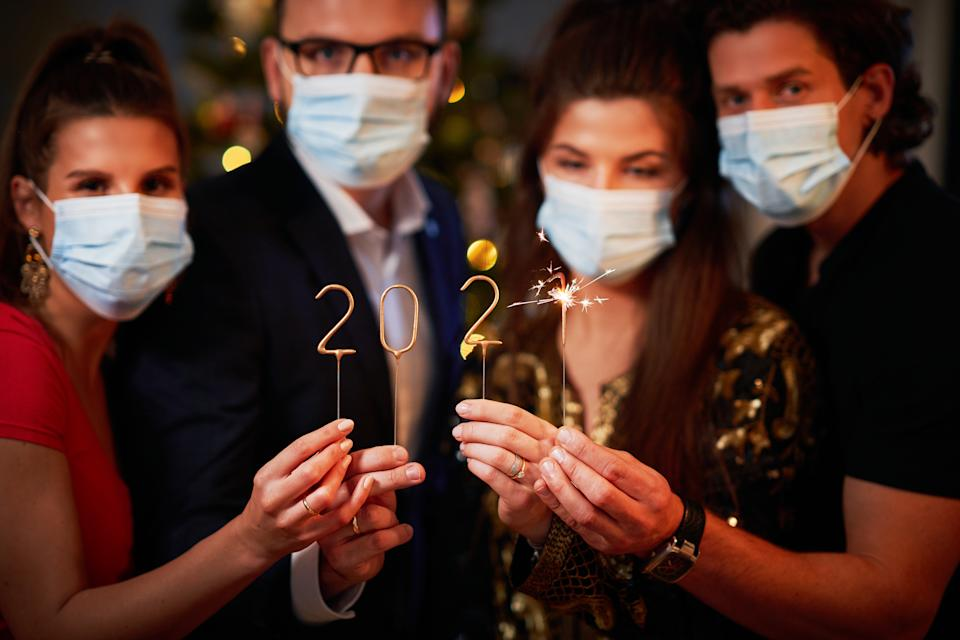 Two beautiful young couples having fun at New Year's Eve Party holding numbers 2020